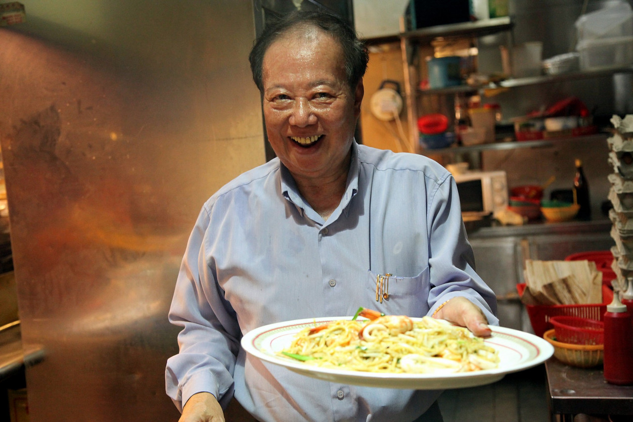 """I have been cooking the Prawn Mee since 1965,"" says Kim as he holds up an old black and white photo of his younger self flanked by his two brothers. Their first Prawn Mee stall was in Changi Village, he also brought out news clippings and numerous awards that his stall has won over the years. He is most proud of the news clipping from the Straits Times food review section, praising his ""Hokkien Mee as outstanding.""<br /> <br /> When the affable hawker first started his business, a bowl of prawn mee soup was only 35 cents he shared. You can't even buy bottled water with that now."