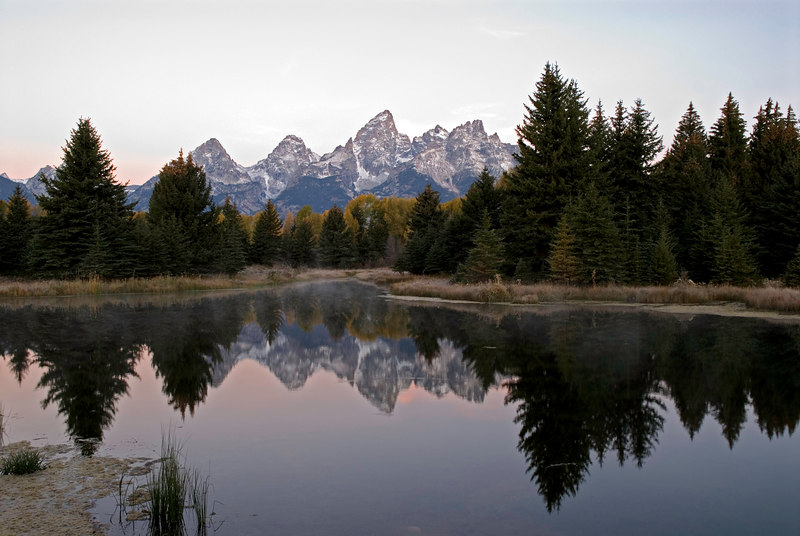Waiting patiently for the sun to rise  delivers this early morning photo of the Grand Tetons and their reflections in this pond made by beavers which is an offshoot of the Snake River as it winds its way through Grand Teton National Park.