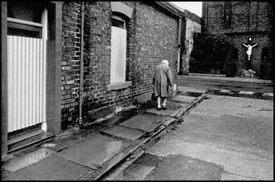 G.B. ENGLAND. Sunderland. An old women trudges past boarded up terraced houses with a statue of Christ beyond. 1974.