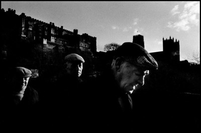 GB.  England.  Durham.  Three men in cloth caps, probably coal miners, with Durham Castle and cathedral in the background. 1974
