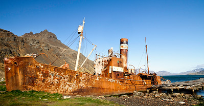 GR125    Rusting wreck by a dock.