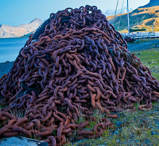 GR129    Pile of rusty chain near the water's edge.