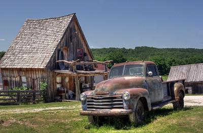 Old Chevy truck parked in front of a shack. Bakersville - a seed store and fantasy town near Mansfield, Missouri. Color, high dynamic range version.