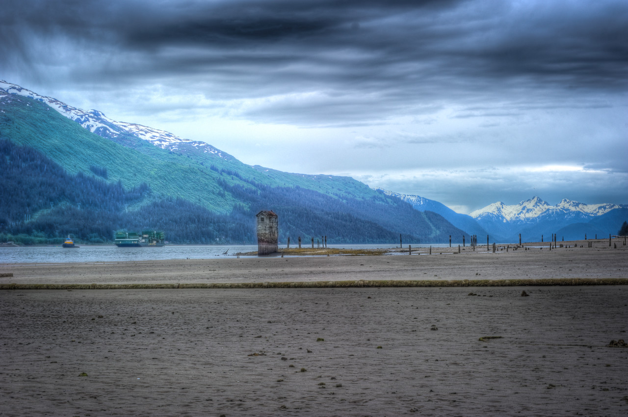 A 3 EV HDR Photograph at Sandy Beach on Douglas Island Alaska near Juneau Alaska.  An Alaska Marine Lines Tugboat pulls a barge up the Gastineau Channel to Juneau, Remnants of the Treadwell Gold Mine are scattered across Sandy Beach and the Pumphouse (a local icon) is visible.  Taken with a Nikon d700, edited in Photomatix & Lightroom.