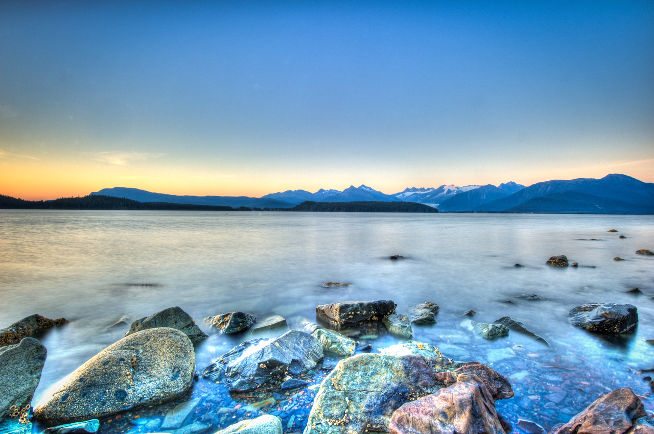 A 7 EV HDR Photograph taken from the North End of Douglas Island Alaska, near Juneau Alaska, taken during the late summer sunset.  Mendenhall Glacier is just visible across the water.  Taken with a Nikon d700, edited in Photomatix & Lightroom.