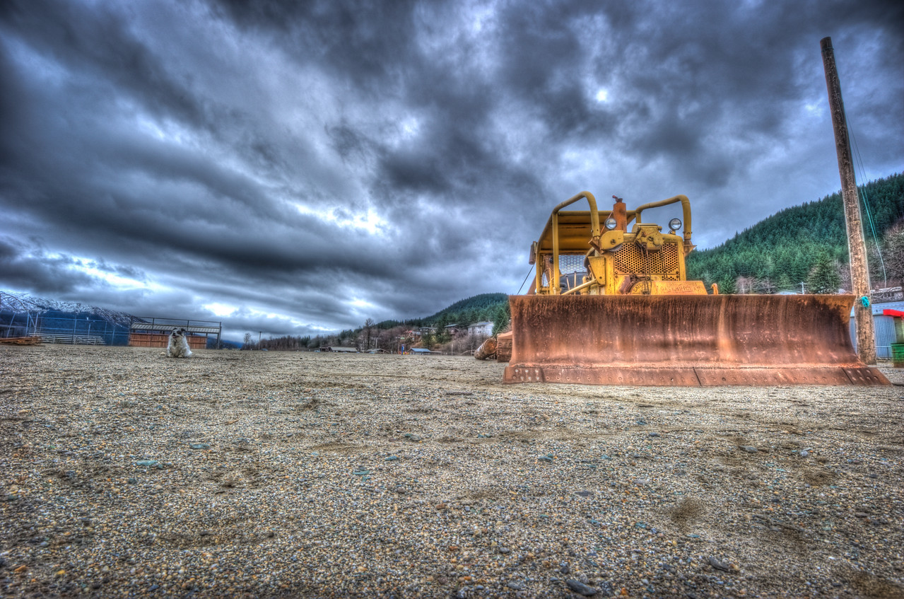 A 7 EV HDR photograph of a bulldozer taken on Douglas Island Alaska, near Juneau Alaska, my little dog Bondo is visible on the left side of the photo juxtaposed against the large machine.  Shot with a Nikon d700, edited in Photomatix & Lightroom.
