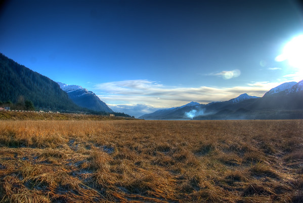 A 3EV HDR photograph taken in the late fall looking South toward Downtown Juneau Alaska, Mt. Juneau on the Left & Mt. Jumbo on Douglas Island is on the Right, notice the vehicle on the left & you can see it moved during each of the 3 exposures.  Shot with a Sony Alpha a300, edited in Photomatix & Lightroom.