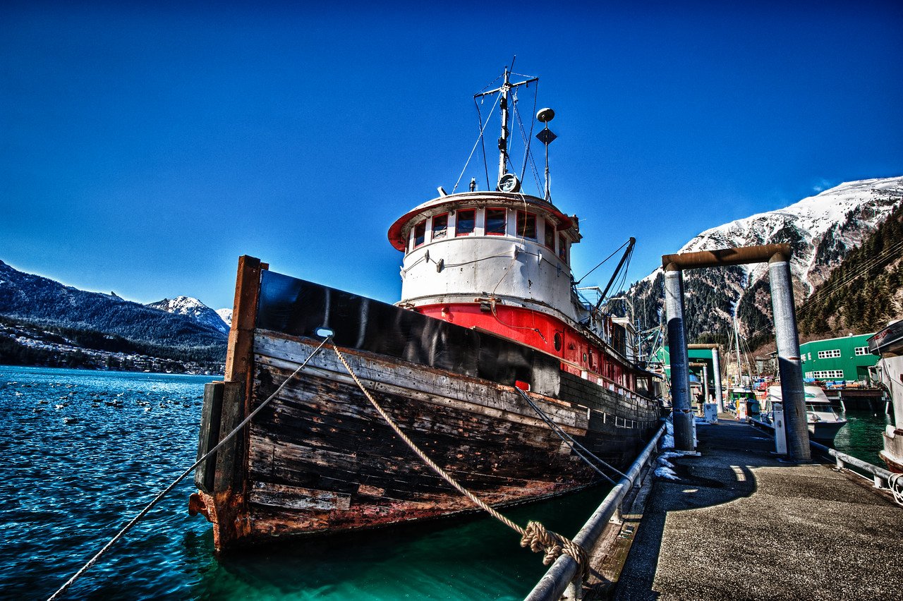 A 7 EV HDR Photograph of a classic Red Tug boat tied up at Juneau Alaska.  Mt Juneau is visible on the right & Douglas Island Alaska is on the left.  Taken with a Nikon d700, edited in Photomatix & Lightroom.