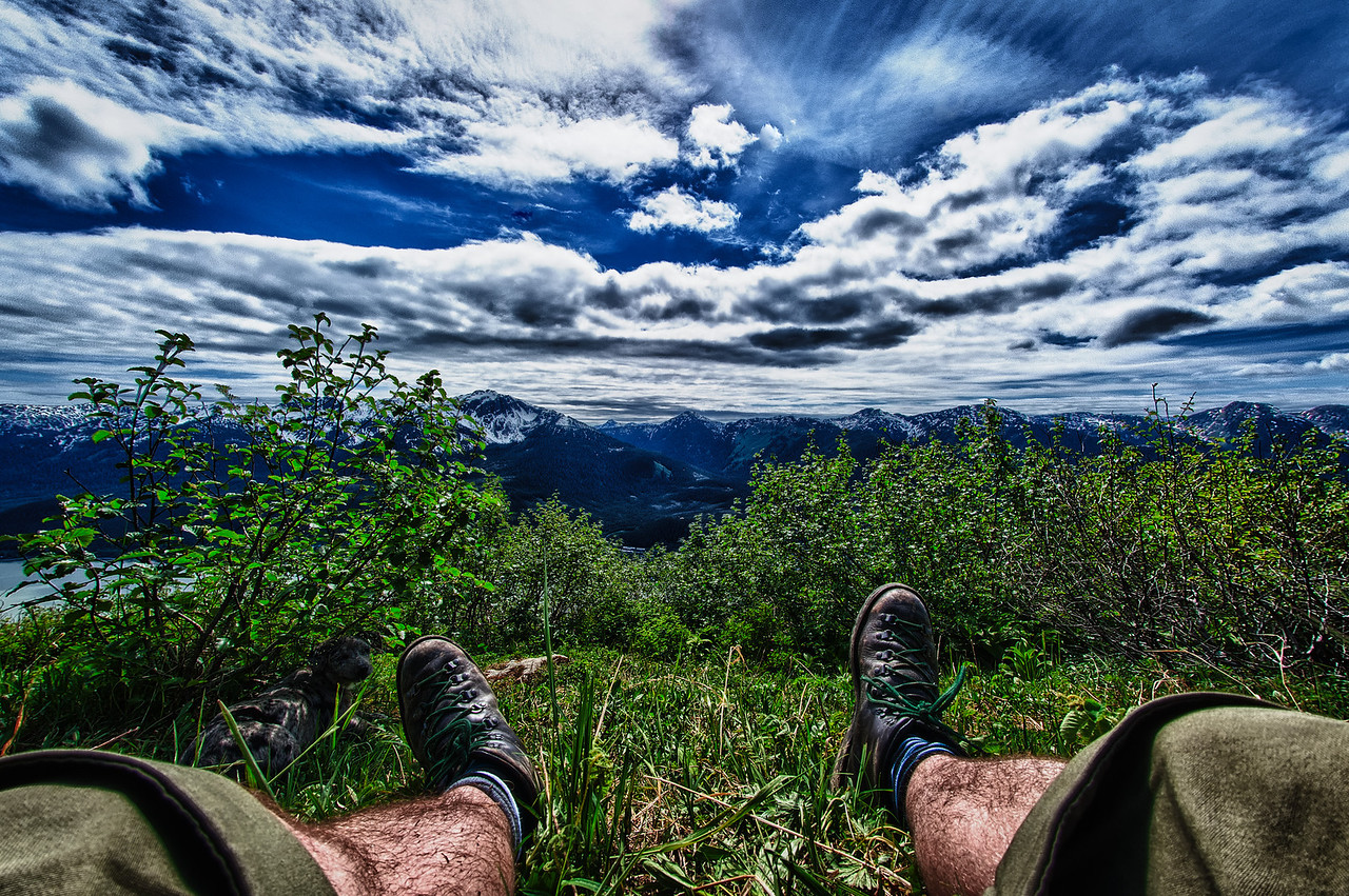 A 5 EV HDR Photograph of me relaxing near the top of Mt. Robert's in Juneau Alaska, with my little dog on the left in the shade.  We are looking to the West toward Douglas Island & Admiralty Island in the distance.  Taken with a Nikon d700, edited in HDR Efex Pro & Lightroom.