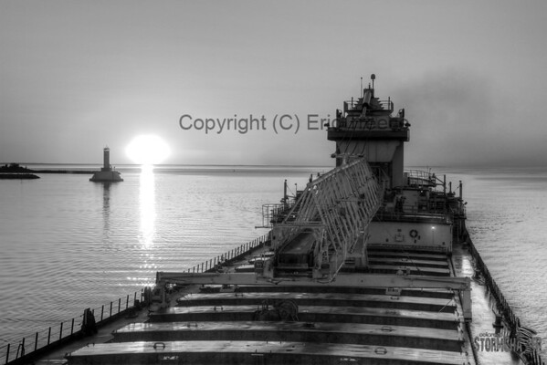 SS Wilfred Sykes heading passed Mackinaw Island and the rising sun.