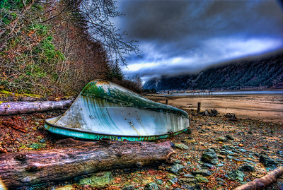 A 9 EV HDR of an overturned beached boat on Douglas Island Alaska near Juneau Alaska (visible in the distance).  Shot with a Sony Alpha a300, edited in Photomatix, Topaz Adjust & Lightroom.