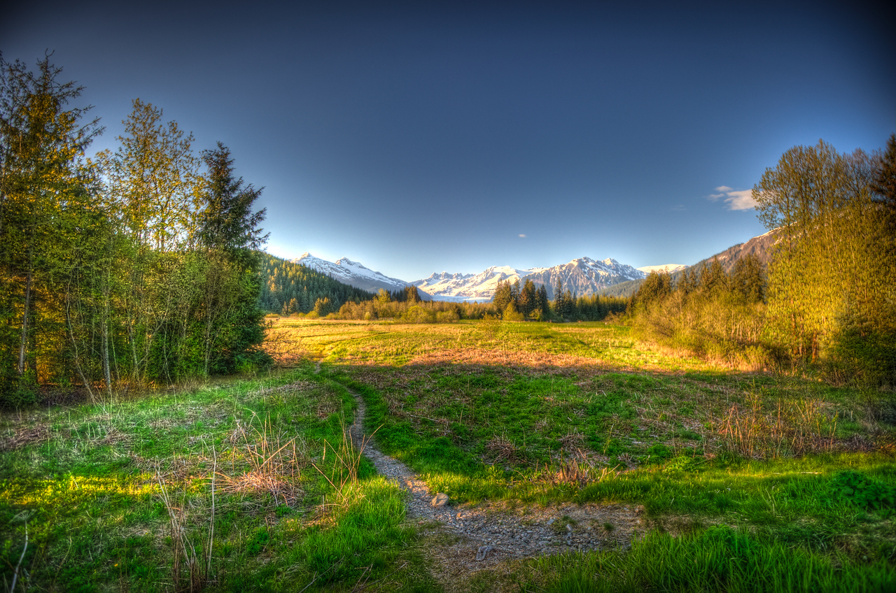A 5 EV HDR Photograph of the Mendenhall Valley near the start of the Brotherhood Bridge Trail in Juneau Alaska.  The Mendenhall Glacier is seen in the distance surrounded by snow covered mountains.  Taken with a Nikon d700, edited in Photomatix & Lightroom.