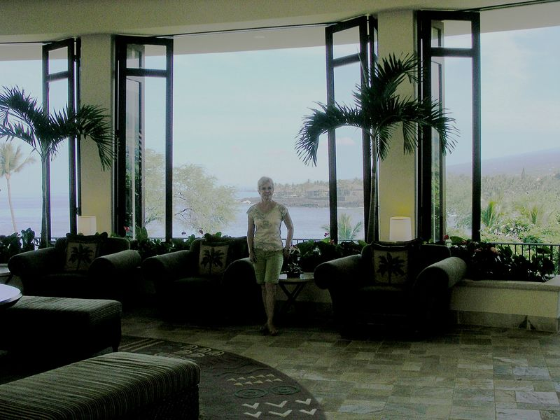 "Mom at our hotel lobby in South Kona overlooking Keauhou Bay. The point facing the ocean to Mom's right at the entrance to the bay is one of the places where the manta rays come to feed at night when the hotel lights are shined out into the water. Unfortunately, we missed the opportunity to go snorkeling with the mantas (another ""next time"") but we were able to see them from the bar at the hotel. The water was so clear when the lights were shined we could see the reef. It was beautiful!"