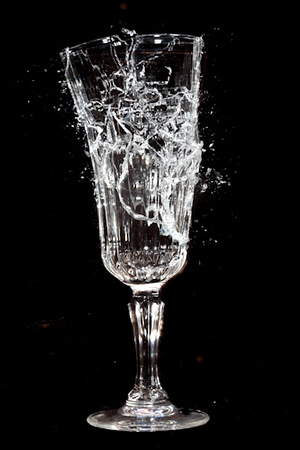 Wine Glass being shattered by a gunshot. High-speed flash triggered by a delayed sound gate.