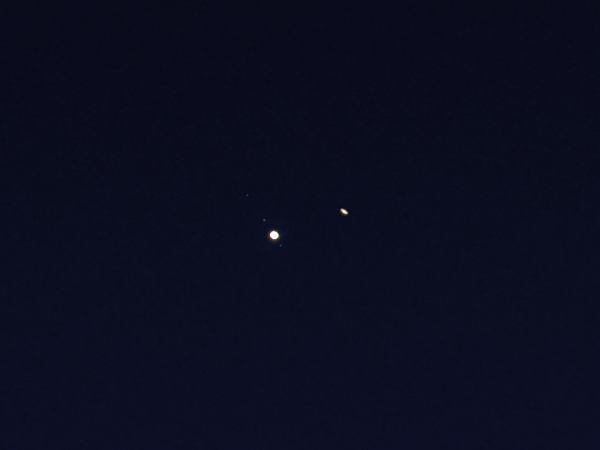 Heavily cropped version of my best shot...I can make out Jupiter and 3 moons and Saturn appears oblong thanks to its rings, but my 200mm lens with 1.4x extender can't resolve the space between the planet and its rings