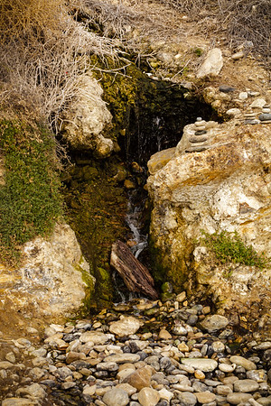 Water continues to trickle on to the beach from this crack in the hillside