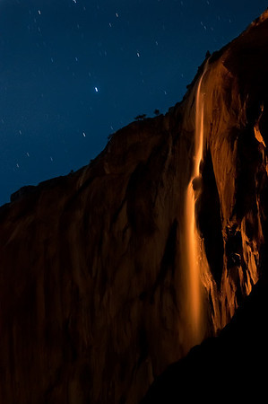 """Many photographers know about Horsetail Falls in Yosemite and that every February it lights up into a """"Fire Falls."""" In fact, I photographed this exact event in February of this year and it was spectacular. Many photographers, however, do not know that the same phenomenon occurs via moonlight on some rare occasions! <br /> <br /> On Saturday, Feb 16th 2011 I woke up at 3am and headed over to the Picnic Grounds at Yosemite National Park. When I arrived the moon was really lighting up the falls but the angle wasn't quite right to turn the falls red. After a couple minutes of setting up and figuring out my camera settings all of a sudden the photos started turning orange! It lasted for about 10 minutes before the falls were completely dark. <br /> <br /> Note that to the human eye the falls appeared white but to the camera it appeared red! The human eye has 2 photo-receptors: rods and cones. Cones are really good at detail and color but require a lot of light. They don't work so well in low light (night). Rods on the other hand, are really good at low light but they can't detect color. So at night, in this scene, our eye only saw the brightness of the falls but the camera sensor saw the beautiful color! <br /> <br /> There is NO saturation change to this. The only thing I did after taking this photo was a small white balance adjustment, some sharpening, and some noise reduction!<br /> <br /> I'd also like to note the difficulties in taking this photo. It was nearly pitch black and the camera cannot focus at all. Additionally, using LiveMode, as I did during the sunset Fire Falls, doesn't work either since the LiveMode displayed a completely black view. I had to set the camera to focus at infinity, took a photo, and then tweaked the focus. I continued this until I got a shot that was in focus. Additionally, since there's so little light I had to bump the ISO wayyyyyy up. Additionally, I had to turn """"Long Exposure Noise Reduction"""" and """"High ISO Noise Reduction"""" off or I w"""