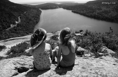 Two young ladies appreciate the view overlooking Jordan Pond in Acadia National Park.