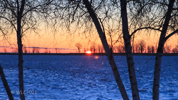 Sunriise over the frozen St Clair River, with wind mills visible on the horizon