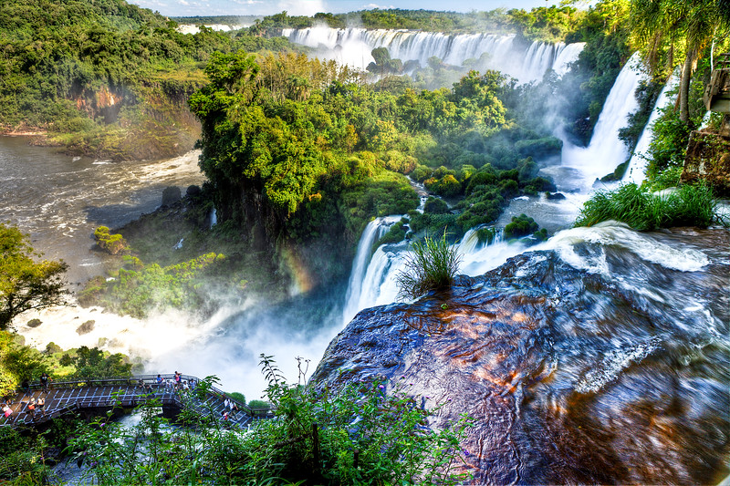 IGUAZU FALLS, Argentina 115.  Sun hits the rocks and brings out rich colors shining through water cascading over the top. upper trail