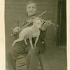 Man playing violin with a dog  on his lap, 1909.  RPPC