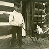Boy with a cart with another child and a dog in front of a chinked log house, ca. 1910.  RPPC