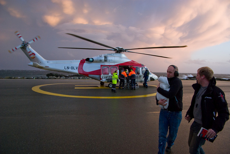 Routine landing<br /> Passengers embarking in the strong wind - helicopter keeps rotors running trusting downwards, to prevent the craft from being blown off the landing.