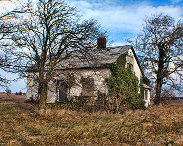 An abandoned house still stands slowly being reclaimed by the nature around it.  Along old US 35 outside of Washington Court House, OH