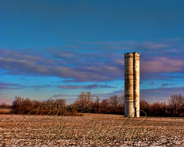 A silo stands alone in a field outside of New Lebanon, OH.  Nothing but corn fields surround it.