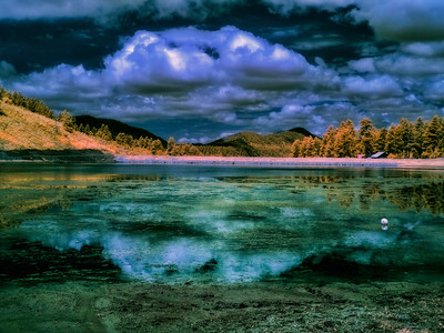 Lake Simpatico in Forest Lakes, Colorado, glows eerily beneath illuminated clouds in infrared