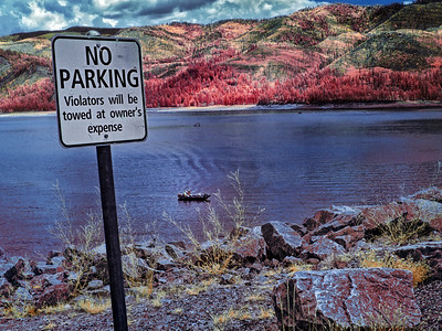Boaters on Vallecito Lake in Vallecito, Colorado, float small beneath the warning sign.  In infrared, the water takes on character unseen by the naked eye.