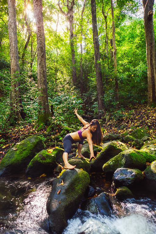 Photo of girl doing yoga by a stream