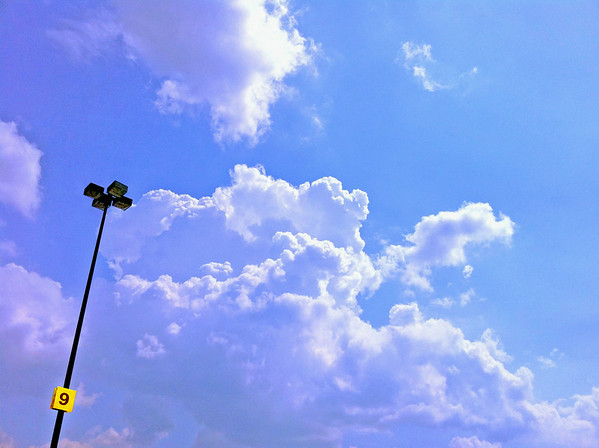 From parking lot at SAMS a light  pole projects against a beautiful sky of cumulus clouds.