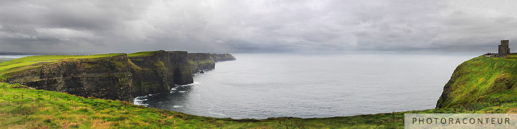 """Storm Approaching Cliffs of Moher"" ~ Dark clouds and rain showers approach the Cliffs of Moher in County Clare, Ireland.  Moments later this storm was directly above, pouring rain and cutting the visibility to nearly nil. O'Brien's Tower on the right was built by Cornelius O'Brien as an observation tower way back in 1835 and was recently restored.  The cliffs have since been given the prestigious recognition as a Global Geopark by the United Nations (UNESCO).  The cliffs are as tall as 702' (214m), stretching over 5 miles (8km).   NOTE: SmugMug limits file sizes to 48 megapixels and does not provide a non-cropped print option for 4:1 panoramics.  This multi-frame stitched photo has an aggregate size of 121 megapixels, with dimensions of 22000x5500.  Thus, prints of this photo up to 15""x60"" are available exclusively through my gallery on Imagekind..  Archival-quality prints are available on paper or canvas.  I am currently looking for on-demand printers that offer prints larger than 60"" wide."