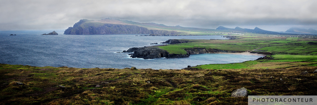 """Clogher Cove"" ~ Sybil Head and the triple peaks known as the Three Sisters appear beyond the cove at An Drum, as viewed from near Clogher Head.  The small white specks on the peninsula are sheep, while the larger specks in the distance are houses. This multi-frame stitched photo has an aggregate size of 48 megapixels."