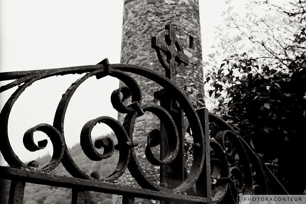 """St. Kevin's Gate"" ~ An old wrought iron gate with a Celtic cross ornament guards the graveyard at the Celtic monastic site in the Glendalough Valley, County Wicklow, Ireland. A thousand-year old round tower appears in the background."