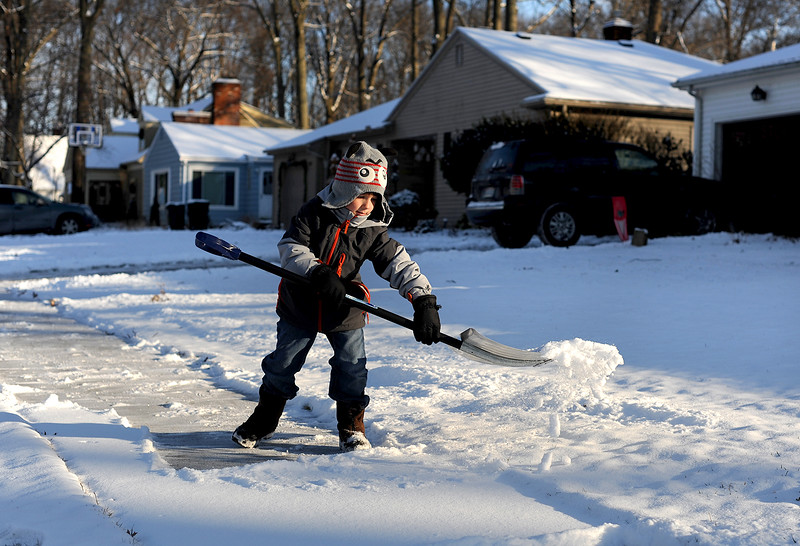 Kaiden Vonya, 6, of Elyria, makes his way down the sidewalk with his snow shovel on Jan. 6 after school.  Vonya said he wasn't excited when it started to snow, but it is fun because his friend Jake, who lives down the street, is shoveling snow as well.  KRISTIN BAUER | CHRONICLE