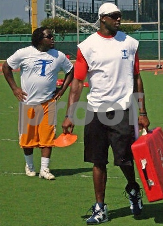 Terrell Owens and a camp coach observe workouts  during T O's 2009 football camp at Duncanville,  High School Stadium (Texas)<br /> Need a photographer for your sports camp? Rates from $375 depending on requirements of client.