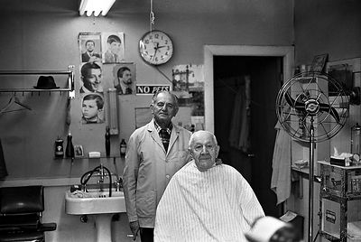 "Papa Green & Henry the Barber - 1979. I followed my grandfather's day-to-day activities as the subject for a college photojournalism project. Captured with a Minolta SRT-201 - 28mm f2.8 lens. I developed film and original prints -- both have tarnished over the years. I recently scanned the negative and restored in Photoshop.   >Papa didn't need a hair cut. It was a ritual that these good friends would get together, share jokes with their thick jewish accents and throw back a shot of  ""schnapps..."""