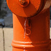 Water dripping from an orange fire hydrant in Columbus, Ohio.
