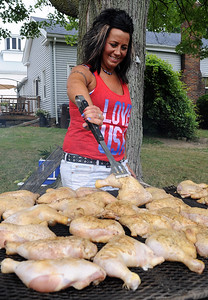 Jill Miller of Rochester cooks chicken for the 97th annual Rochester Homecoming on Monday, July 4.  STEVE MANHEIM/CHRONICLE