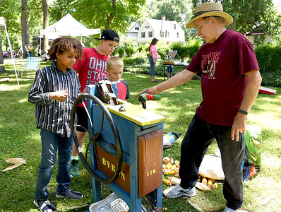 KRISTIN BAUER | CHRONICLE  London Mudd, 9, Jackson Smith, 10, and Joseph Smith, 6, all of Elyria, learn how to shell corn in a 100-year old corn sheller on Sunday afternoon, July 10 during the annual Ice Cream Social hosted by the Lorain County Historical Society.
