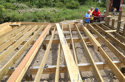 Mindy Shawver and Tim Johnson of the Elyria Lowe's store and Ryco Crawford of the Rocky River Lowe's work on the new deck at the Sunflowers for Maria site in Avon. BRUCE BISHOP/CHRONICLE