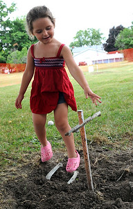 Jaylean Speicher, 3, of Rochester, plays  horseshoes at the the 97th annual Rochester Homecoming on Monday, July 4.  STEVE MANHEIM/CHRONICLE