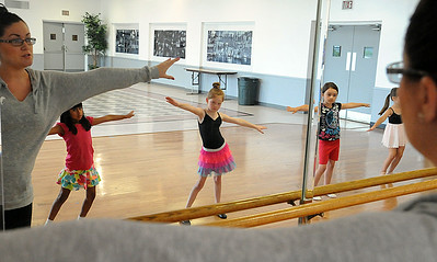 Instructor Colleen Dziak, left,  teaches ballet basics to Adrianna Rotuno, Bella Truxall , Alyssa Thompson and Khloe Racz on the first day of Ballet and Jazz Dance Combo class at Elyria YWCA on July 7.  The class continues through the week.  Steve Manheim