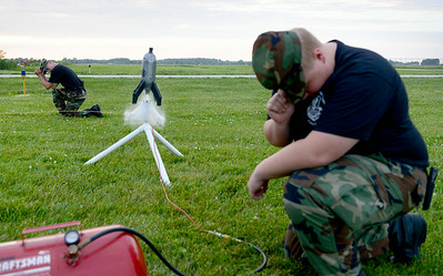 U.S. Air Force Auxiliary Cadet 2nd Lt. James Carey, 15, of Lorain, and Adam Wagner, 16, of Amherst, launch a rocket made out of a 2-liter bottle at the Lorain County Regional Airport on July 1. KRISTIN BAUER | CHRONICLE
