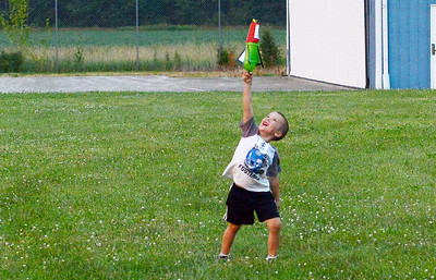 Casey Haff, 6, of Amherst runs to retrieve his rocket after participating in the U.S. Air Force Auxiliary's rocket launch experiment at the Lorain County Regional Airport on July 1. KRISTIN BAUER | CHRONICLE