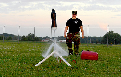 U.S. Air Force Auxiliary Cadet 2nd Lt. Adam Wagner, 16, of Amherst, helps launch a rocket made out of a 2-liter bottle at the Lorain County Regional Airport on July 1.   KRISTIN BAUER | CHRONICLE
