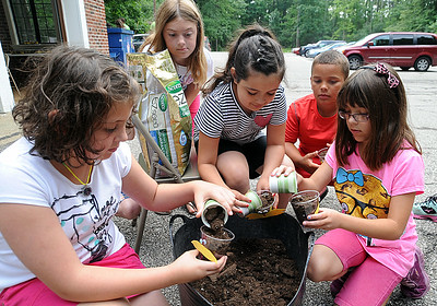 """Victoria Jones, left, Kendyl Lynn, Emerson Nazario, Jacob McEntee and Delaney Miller, pour soil into a cup to plant grass seeds at Environmental Science Camp at Finwood Estate in Elyria on July 7.   This project is inspired by a reading of """"The Lorax"""" by Dr. Suess.   The week-long Elyria Parks and Recreation Dept. camp is for kids 6-12 years old.   Steve Manheim"""