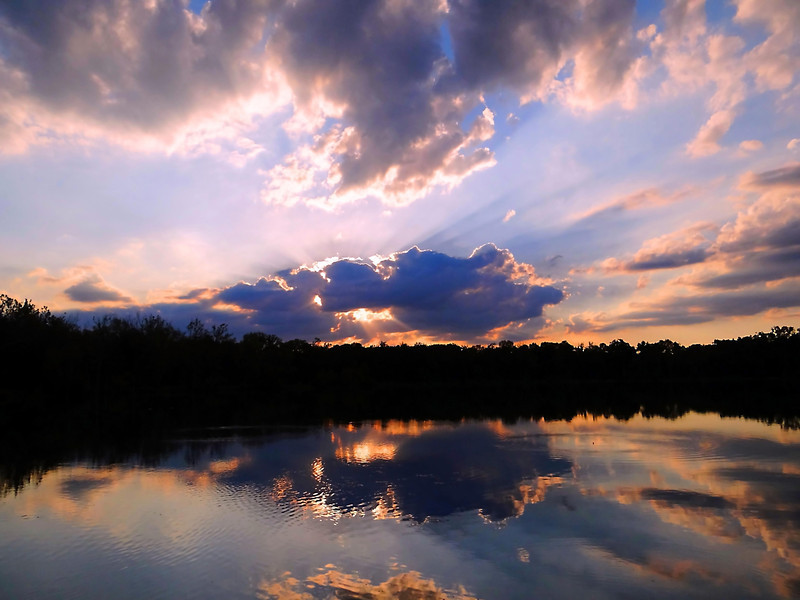Prairie Oaks sunset in June with reflections in the still water of the quarry lake.   Photographed at Prairie Oaks Metro Park outside Galloway, Ohio.